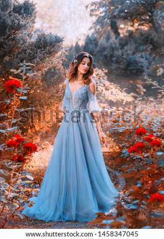 sad princess walks in fading red orange autumn garden tree withered plants, lady dark hair chic light blue dress red roses sadness, fantasy art photo young attractive girl creative colorful image #1458347045