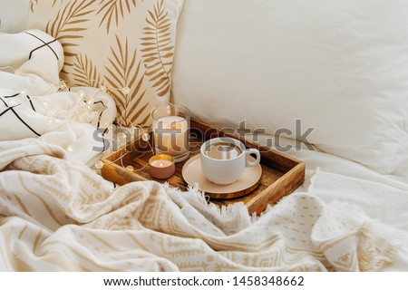 Wooden tray of coffee and candles on bed. White bedding sheets with striped blanket and pillow. Breakfast in bed. Hygge concept. #1458348662
