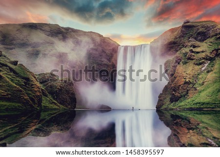 Icelandic Landscape. Classic long exposure view of famous Skogafoss waterfall with reflections. Dramatic Scenery of Iceland during sunset. majestic Skogafoss Waterfall in countryside with colorful sky #1458395597