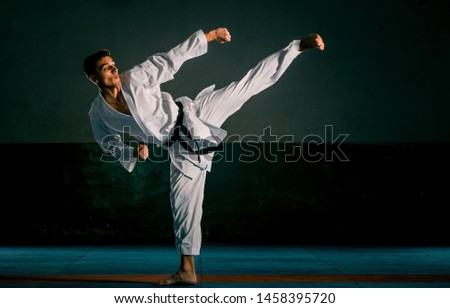 A young strong man in a white kimono for sambo, jiu jitsu and other martial arts with a black belt training in gym, low key, high contrast Royalty-Free Stock Photo #1458395720