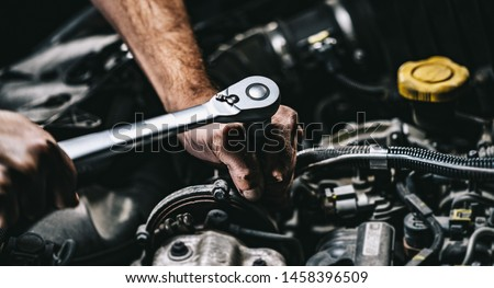Auto mechanic working on car engine in mechanics garage. Repair service. authentic close-up shot Royalty-Free Stock Photo #1458396509