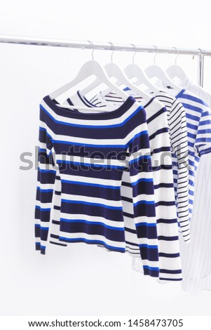 Row of different stripy clothing, shirt with long sleeve shirt on hanging  #1458473705