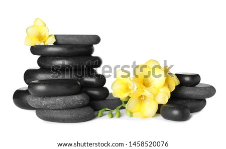 Stack of black spa stones and fresh flowers isolated on white #1458520076