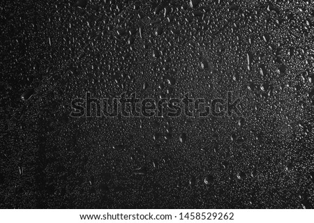 Glass with rain drops against dark background #1458529262