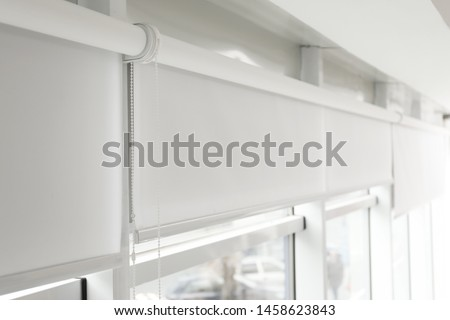 Modern window with white roller blinds indoors Royalty-Free Stock Photo #1458623843