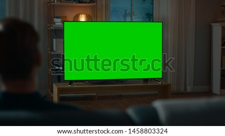 Man Watches Green Mock-up Screen TV while Sitting on a Couch at Home in the Evening. Cozy Living Room with Warm Lights.