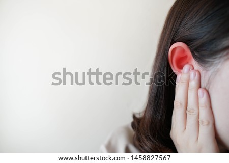 Young woman suffering from ear pain and tinnitus. Cause of earache includes otitis, earwax buildup, a foreign object in the ear, sinus infection or changes in air pressure. Ear disease concept. #1458827567