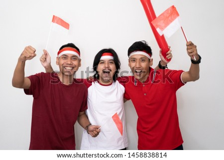 asian young male supporter of indonesia. holding flag and wearing red shirt. indonesia independence day celebration #1458838814
