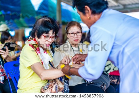 Buriram, Thailand - July 2019, Indigenous Senior Man with Tray with Pedestal of Flowers and Garland making rice offering for  special occasions and events in Buddhist, Buriram, Thailand. #1458857906