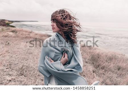 Attractive young woman standing on a windy cold beach wrapped in warm blanket with flower in her hand. #1458858251