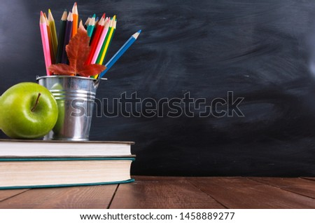 Stack of books, green apple, colored pencils and autumn leaf on wooden desk. Classroom blackboard with copy space in background. Education, back to school concept #1458889277