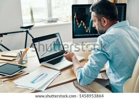 Rear view of man in smart casual wear analyzing stock market data while sitting in the office          #1458953864