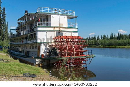 tourists boarding a sternwheel river boat to cruise the Chena River near Fairbanks in Alaska with the river and forest in the background #1458980252