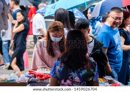 Chicago,IL/USA-July 21st 2019:  Chinese woman is selling goods outside local shop during the Chinatown summer festival in Chicago. many items in the market that tourist are eager to  buy. #1459026704