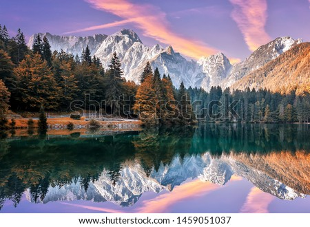 Impressive Autumn landscape during sunset.  The Fusine Lake in front of the Mongart under sunlight. Amazing sunny day on the mountain lake. concept of an ideal resting place. Creative image.