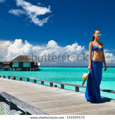 Woman on a tropical beach jetty at Maldives #145909574