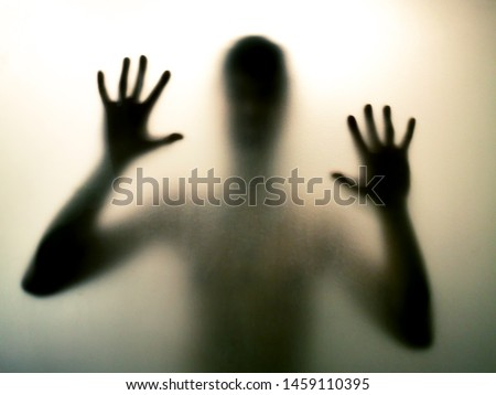 Horror man behind the matte glass in black and white. Blurry hand and body figure abstraction. Halloween background. Murder concept. Criminal concpet. #1459110395