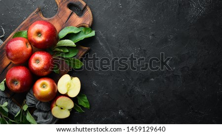 Fresh red apples with green leaves on a black background. Fruits. Top view. Free space for text.