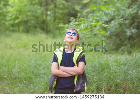 Trendy boy in a trendy blue sunglasses and a bright vest in the summer on a background of green nature. #1459275134