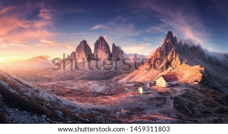 Mountain valley with beautiful house and church at sunset in autumn. Landscape with buildings, high rocks, colorful sky, clouds, sunlight. Mountains in Tre Cime park in Dolomites, Italy. Italian alps Royalty-Free Stock Photo #1459311803