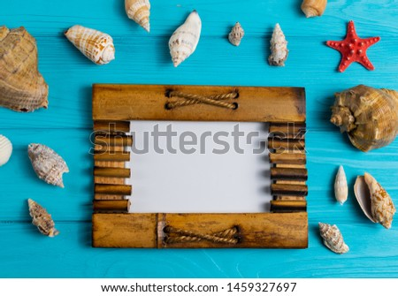 Wooden picture photo frame on blue wooden background with different sea shells for your text or picture