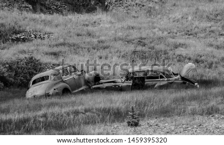 Black and white image of two old, abandoned derelict vintage cars, autos from bygone era in Cripple Creek, Colorado. Sad, desolate, decayed, forgotten, ghostly. #1459395320