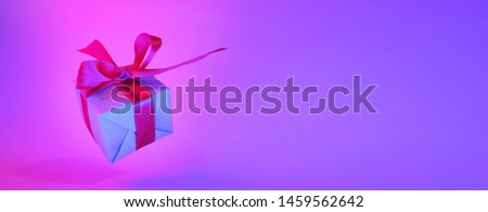 Gift box with red ribbon on trendy neon color background. zero gravity banner. levitation. copyspace. Concept sales, discount price, christmas presents and shopping.
