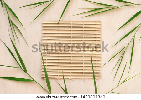 Green bamboo leaves and bamboo mat, asian style background, top view, copy space. Trendy bamboo leaves flat lay on white wooden background. #1459601360