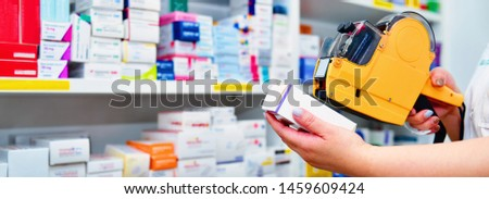 Hand of the pharmacist using yellow labeling gun for sticking price label of medicine in pharmacy drugstore.banner size #1459609424