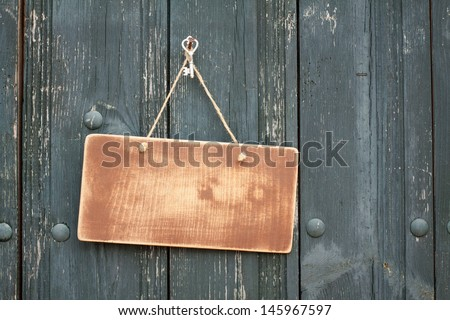 Wooden signboard with rope hanging on planks background