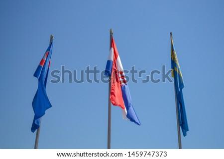 MAKARSKA, CROATIA - JUNE 21: National flag of Croatia and region of Dalmatia on poles in Makarska, Croatia on June 21, 2019. #1459747373