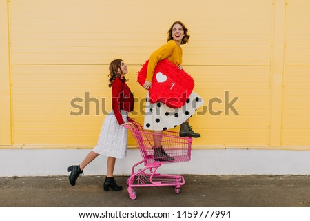 Adorable sisters having fun during shopping. Two glamorous girls posing with heart symbol. #1459777994