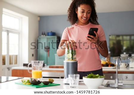 Woman Using Fitness Tracker To Count Calories For Post Workout Juice Drink He Is Making #1459781726