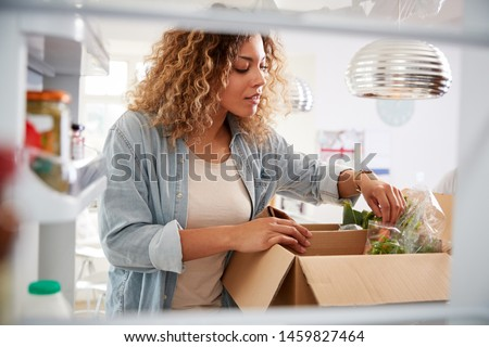 View Looking Out From Inside Of Refrigerator As Woman Unpacks Online Home Food Delivery #1459827464