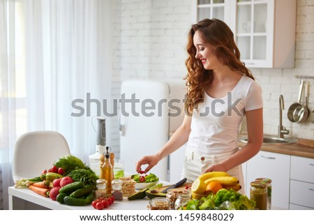 Young happy woman preparing tasty salad in the beautiful kitchen with green fresh ingredients indoors. Healthy food and Dieting concept. Loosing Weight #1459848029