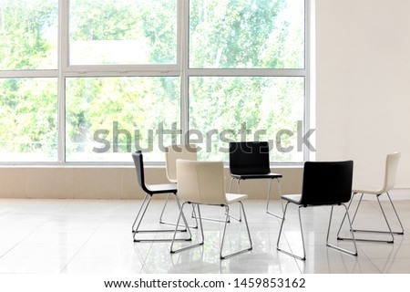 Empty chairs prepared for group therapy indoors #1459853162