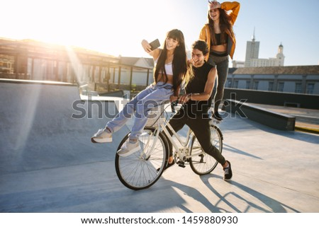 Woman sitting on the bike handlebar taking selfie with friends. Young woman taking a self portrait with her friends on bicycle.