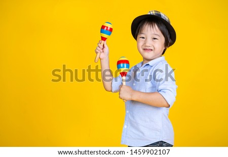 Portrait of little cute asian boy playing the maracas isolated on yellow background with copy space, preschool play group, music learning by doing and education concept #1459902107