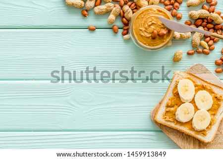 Make sandwiches with banana and peanut butter in glass bowl, knife on mint green wooden background top view copyspace #1459913849