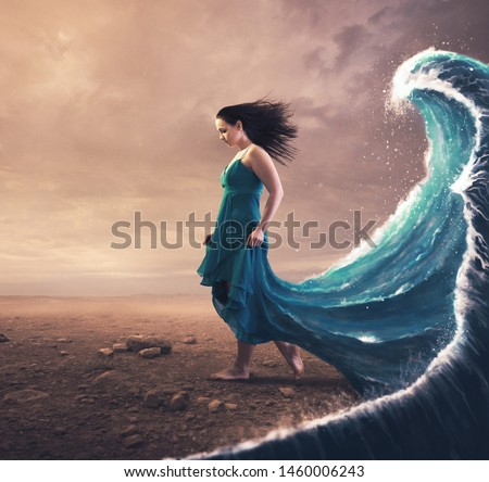 A woman with a blue dress and large wave behind her.  Royalty-Free Stock Photo #1460006243