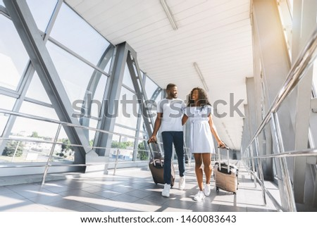 On way to honeymoon. African-american couple travelers with suitcases at airport, freee space #1460083643