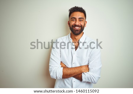 Young indian man wearing elegant shirt standing over isolated white background happy face smiling with crossed arms looking at the camera. Positive person. #1460115092