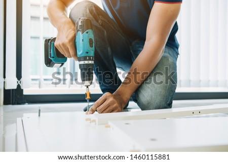 Service man assembling furniture for customer, Delivery service furniture store and assembling for buyer. #1460115881