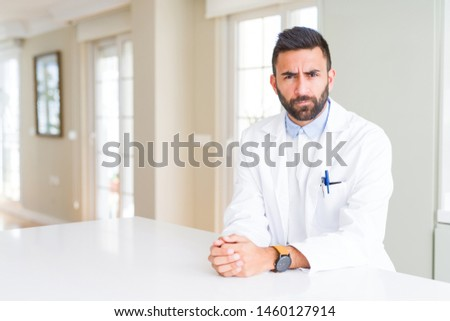Handsome hispanic doctor or therapist man wearing medical coat at the clinic skeptic and nervous, frowning upset because of problem. Negative person. #1460127914