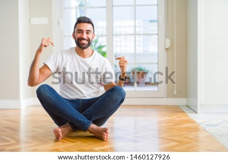 Handsome hispanic man wearing casual t-shirt sitting on the floor at home looking confident with smile on face, pointing oneself with fingers proud and happy. #1460127926