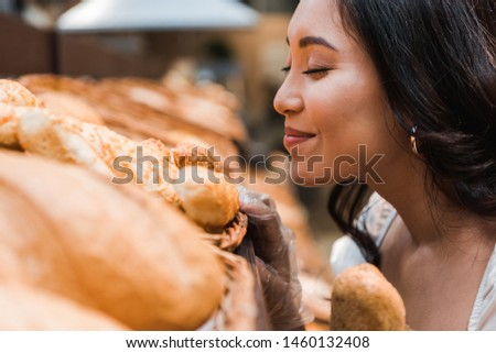 selective focus of cheerful asian woman smiling while smelling bread in supermarket  #1460132408