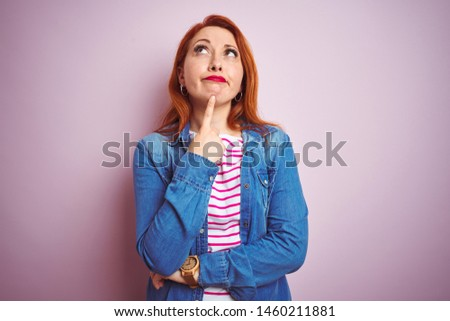 Beautiful redhead woman wearing denim shirt and striped t-shirt over isolated pink background Thinking concentrated about doubt with finger on chin and looking up wondering #1460211881