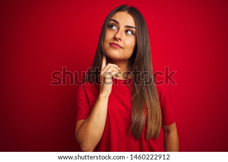 Young beautiful woman wearing t-shirt standing over isolated red background with hand on chin thinking about question, pensive expression. Smiling with thoughtful face. Doubt concept.