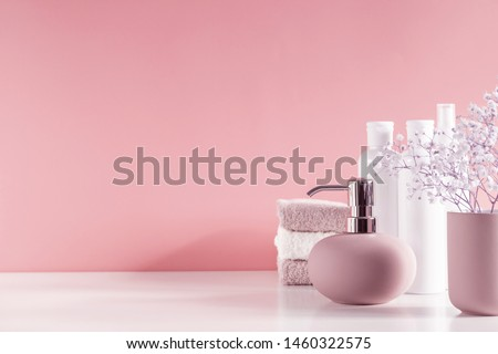 Soft light bathroom decor in pastel pink color, towel, soap dispenser, white flowers, accessories on pastel pink shelf. Elegant decor bathroom interior. #1460322575