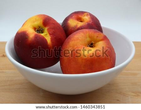 White bowl of fresh peaches on wooden background #1460343851